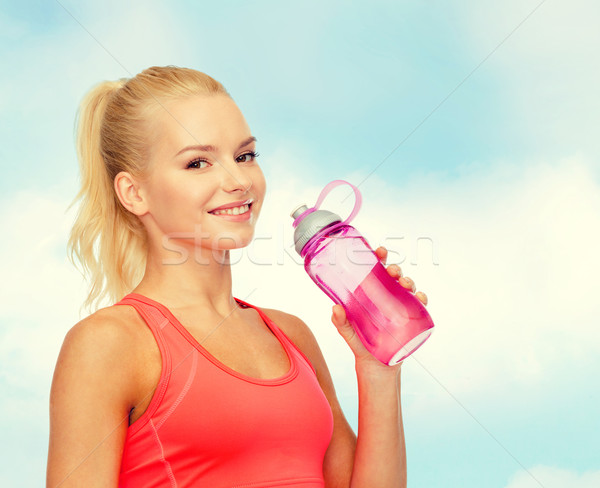 smiling sporty woman with water bottle Stock photo © dolgachov