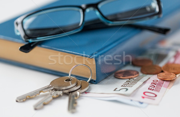 close up of book, money, glasses and keys on table Stock photo © dolgachov