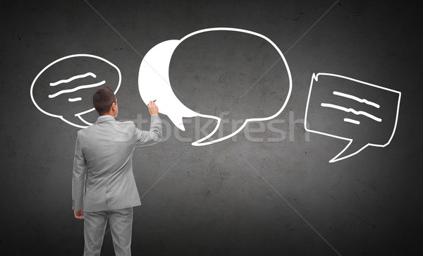 businessman drawing text bubbles from back Stock photo © dolgachov
