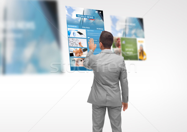man with virtual projection of business news Stock photo © dolgachov