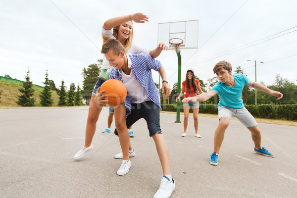 group of happy teenagers playing basketball Stock photo © dolgachov