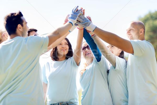 group of volunteers making high five in park Stock photo © dolgachov