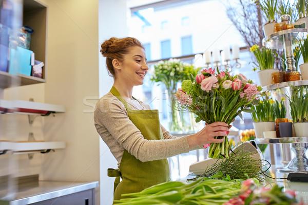 smiling florist woman making bunch at flower shop Stock photo © dolgachov