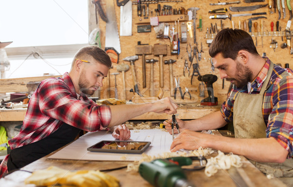 workmen with blueprint and dividers at workshop Stock photo © dolgachov
