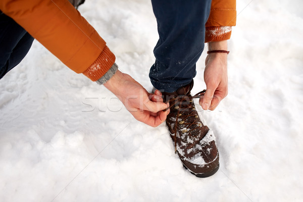 close up of man tying boot shoelaces in winter Stock photo © dolgachov