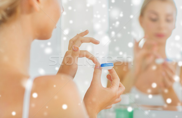 young woman applying contact lenses at bathroom Stock photo © dolgachov