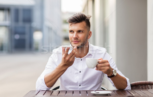 man with coffee and smartphone at city cafe Stock photo © dolgachov