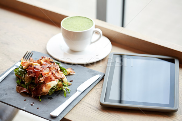 prosciutto ham salad with tablet pc at restaurant Stock photo © dolgachov