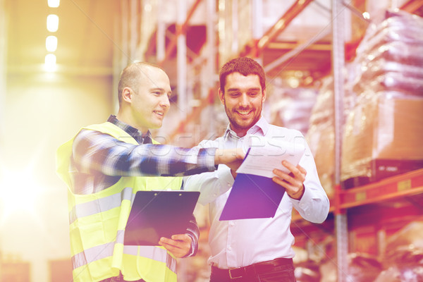worker and businessmen with clipboard at warehouse Stock photo © dolgachov
