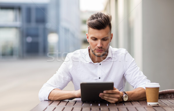 man with tablet pc and coffee at city cafe Stock photo © dolgachov
