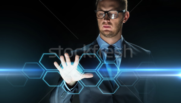 businessman touching virtual hexagonal projection Stock photo © dolgachov