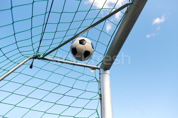 soccer ball flying into football goal net over sky Stock photo © dolgachov