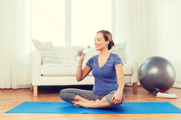 happy woman with water bottle exercising at home Stock photo © dolgachov