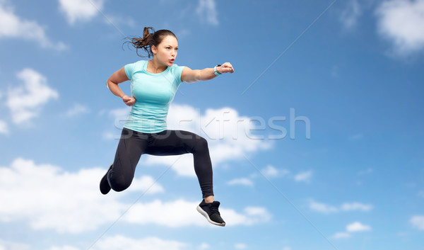 sporty woman jumping in fighting pose over sky Stock photo © dolgachov