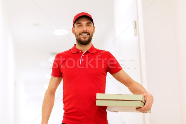 happy delivery man with pizza boxes in corridor Stock photo © dolgachov
