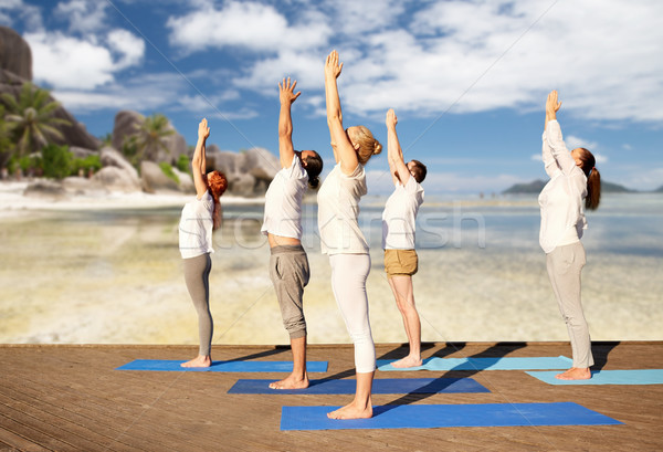 group of people making yoga exercises over beach Stock photo © dolgachov