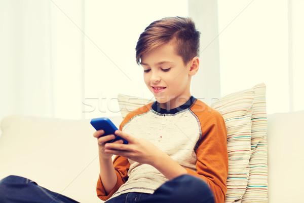 Fiú okostelefon sms chat játszik otthon szabadidő Stock fotó © dolgachov