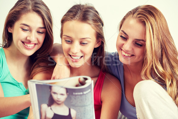 Stock photo: friends or teen girls reading magazine at home