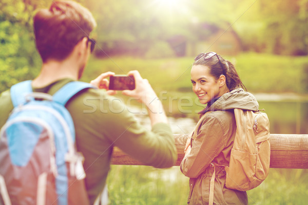 couple with backpacks taking picture by smartphone Stock photo © dolgachov