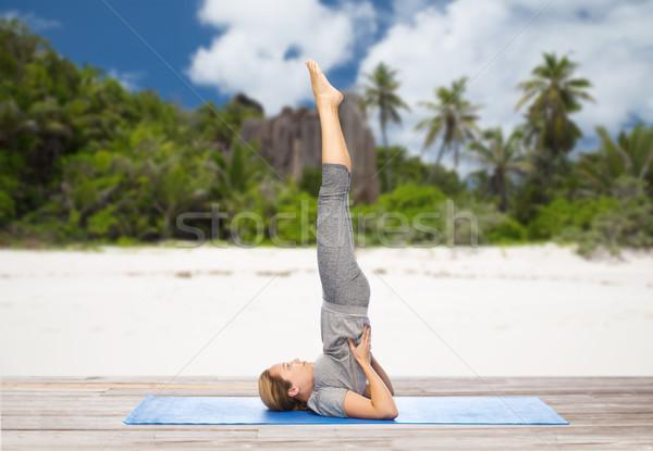 woman making yoga in shoulderstand pose on beach Stock photo © dolgachov