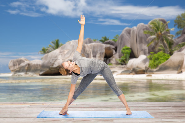 Femme yoga triangle posent plage fitness Photo stock © dolgachov