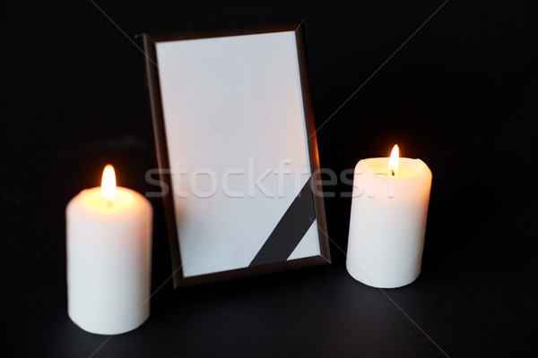 black ribbon on photo frame and candles at funeral Stock photo © dolgachov