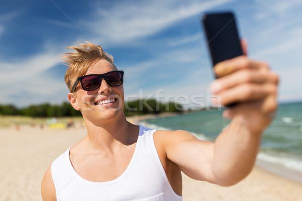 Férfi okostelefon elvesz nyár tengerpart ünnepek Stock fotó © dolgachov