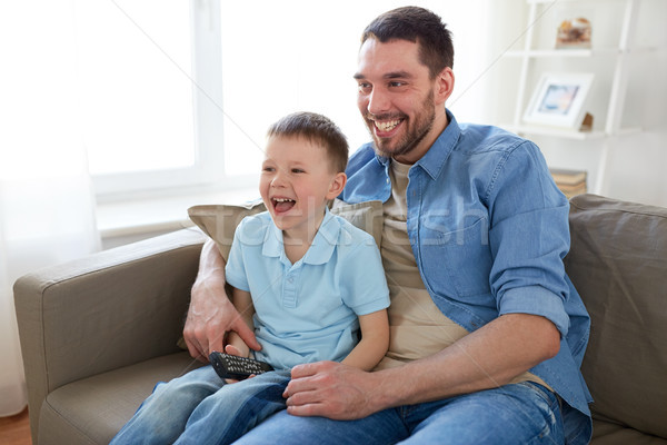 father and son with remote watching tv at home Stock photo © dolgachov