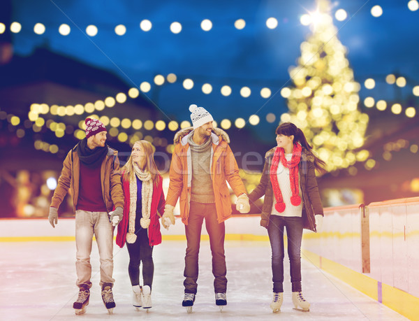 happy friends at christmas skating rink Stock photo © dolgachov