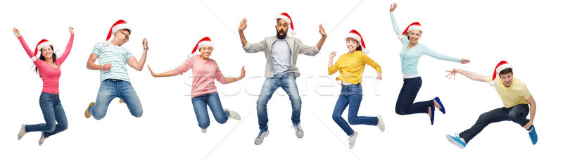 happy people in santa hats jumping in air Stock photo © dolgachov