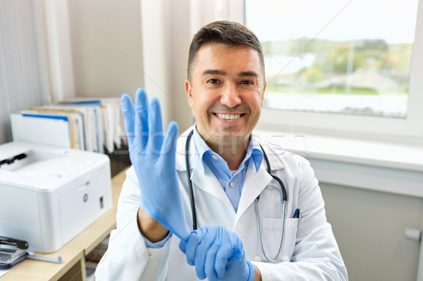 smiling doctor with protective gloves at clinic Stock photo © dolgachov