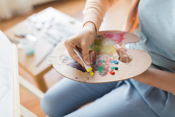 artist applying paint to palette at art studio Stock photo © dolgachov