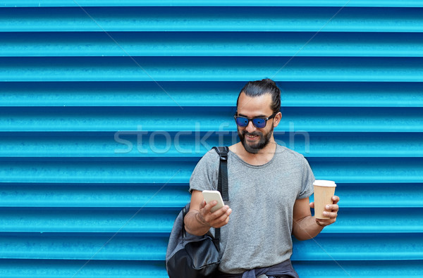 man with coffee cup and smartphone over blue wall Stock photo © dolgachov