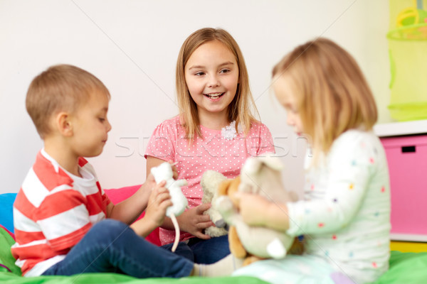 happy kids playing with plush toys at home Stock photo © dolgachov