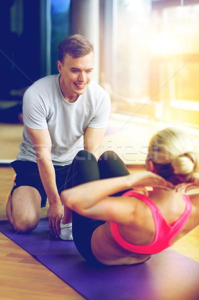 Mosolygó nő férfi edző testmozgás tornaterem sport Stock fotó © dolgachov
