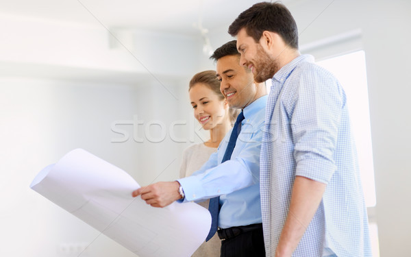 realtor showing blueprint of new home to couple Stock photo © dolgachov