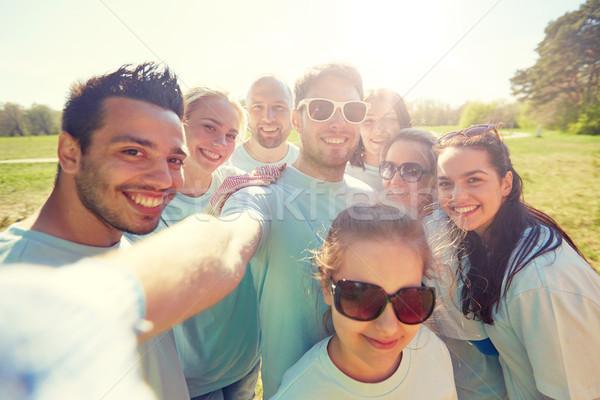 group of volunteers taking selfie by smartphone Stock photo © dolgachov