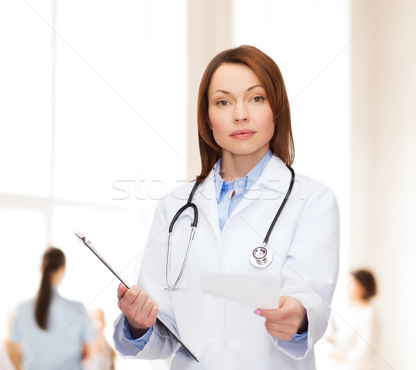 calm female doctor with clipboard Stock photo © dolgachov