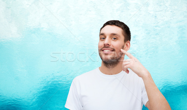 smiling young handsome man pointing to cheek Stock photo © dolgachov