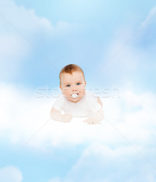 smiling baby lying on cloud with dummy in mouth Stock photo © dolgachov