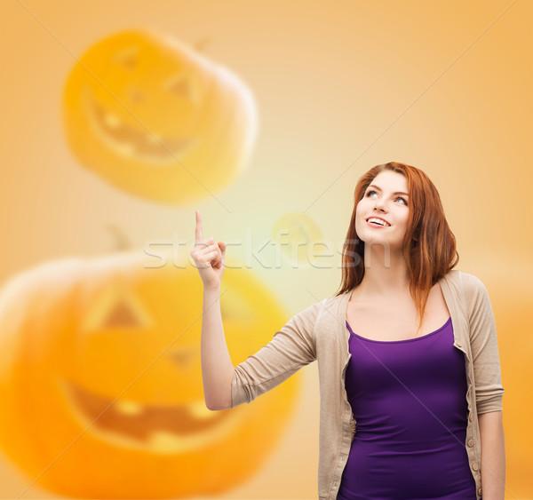 smiling teenage girl pointing finger up Stock photo © dolgachov