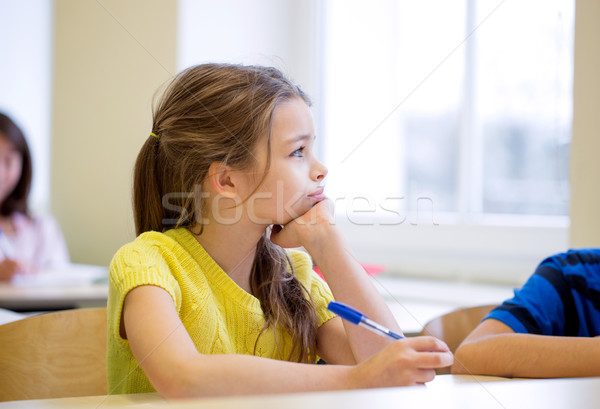 school girl with pen being bored in classroom Stock photo © dolgachov