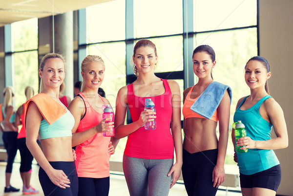 group of women with bottles of water in gym Stock photo © dolgachov
