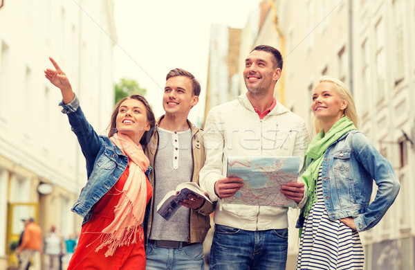 group of smiling friends with city guide and map Stock photo © dolgachov
