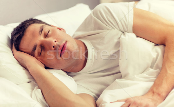 handsome man sleeping in bed Stock photo © dolgachov