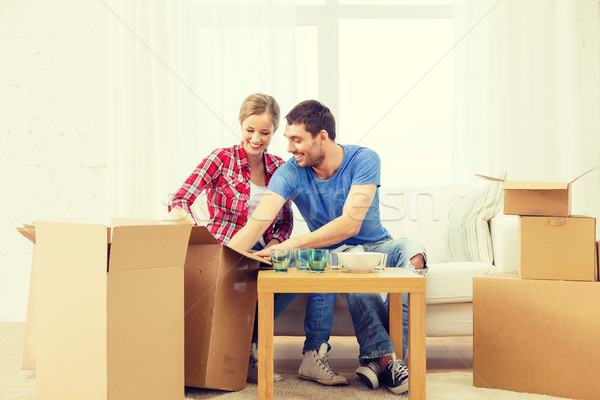 smiling couple unpacking kitchenware Stock photo © dolgachov