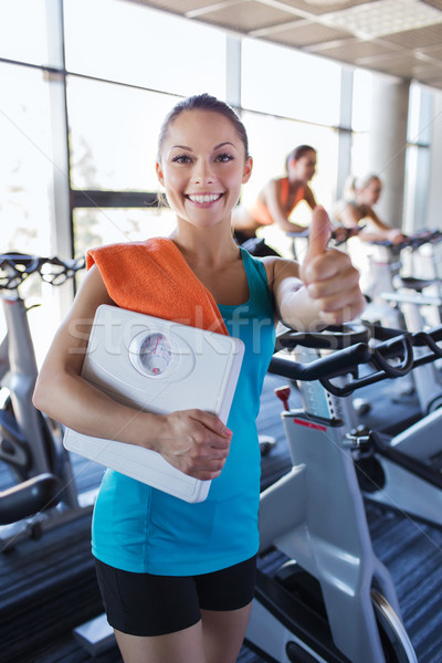 smiling woman with scales and towel in gym Stock photo © dolgachov