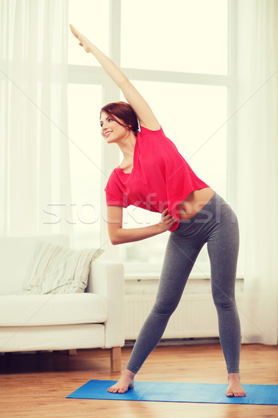 smiling teenage girl streching at home Stock photo © dolgachov