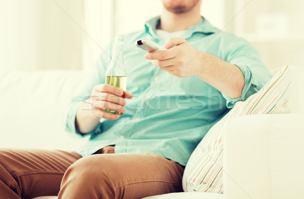 man with beer and remote control at home Stock photo © dolgachov