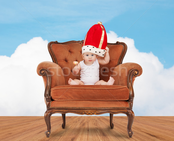 baby in royal hat with lollipop sitting on chair Stock photo © dolgachov